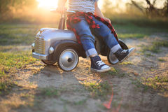 Kid sneakers during car riding in the park Stock Images