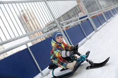 Kid on a snow scooter Royalty Free Stock Images