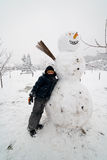 Kid and snowman Stock Images