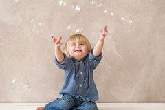 Kid with soap bubbles Stock Photos