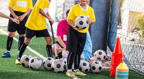 Kid soccer ball and soccer training equipment on green artificial turf. Soccer Academy. kid soccer player and coach are pump air in to a football stock image