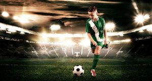 Kid - soccer player. Boy forward in football sportswear on stadium with ball. Sport concept. Royalty Free Stock Image