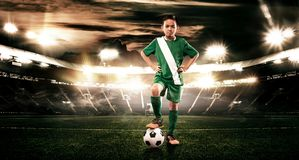 Kid - soccer player. Boy forward in football sportswear on stadium with ball. Sport concept. stock images