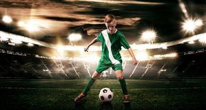 Kid - soccer player. Boy forward in football sportswear on stadium with ball. Sport concept. stock image