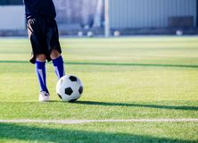 Kid soccer player speed run to shoot ball to goal on green grass royalty free stock images