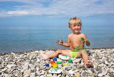 Kid soiled by paints on beach. Kid soiled by paints sits on beach against sea Royalty Free Stock Photo