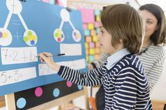 Kid Solving Math Exercises. Cute boy solving graphic math exercises at kindergarten, under educator observation stock images