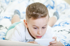 Kid with spartphone. Adorable kid playing with smartphone on the bed Stock Image