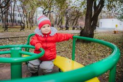 The child is spinning on a swing in the playground in the park. The kid is spinning on a swing in the playground in the park royalty free stock photo