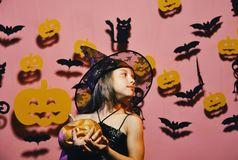 Kid in spooky witches costume holds carved pumpkin. Halloween party and decorations concept. Girl with romantic face Stock Photography