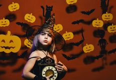 Kid in spooky witches costume holds old clock. Halloween party and decorations concept. Little witch wearing black hat. Girl with concerned face on bloody red royalty free stock photos