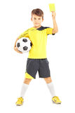 Kid in sportswear holding soccer ball and yellow card Stock Photography