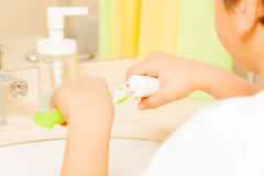Kid spreading toothpaste on green toothbrush Stock Photo