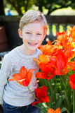 Kid at spring. Beautiful little boy enjoying springtime by the blooming tulips in the park Royalty Free Stock Images