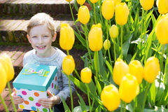 Kid at spring. Smiling boy holding nice present at spring blooming time Royalty Free Stock Photo