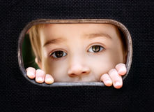 Kid spying through the hole. Curious kid spying through the hole in the wooden wall on playground royalty free stock images