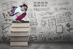 Kid squat on books with scribble at wall Royalty Free Stock Images