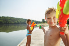 Kid with a squirt gun at a lake. Spraying his sister with water stock photography