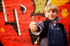 Kid standing in front of a graffiti wall Stock Images