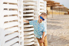 Kid standing near the White Plastic Folding Sun Loungers on the Royalty Free Stock Photo