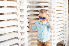 Kid standing near the White Plastic Folding Sun Loungers on the Royalty Free Stock Images