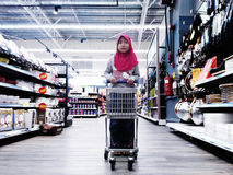 Kid standing with a trolley at a supermarket Stock Photography