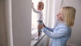 Mother with her baby boy looking at window. Kid stands on the windowsill. Closeup of beautiful happy mother with her baby boy standing at big window and looking stock video footage