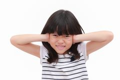 Kid with stressful emotional feeling. Asian kid girl express stress face and raise her hand close her ears. Put on black striped white T-shirt. isolate on white stock photo