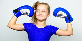 Kid strong and healthy. Girl child strong with boxing gloves posing on grey background. She feels strong and independent stock image