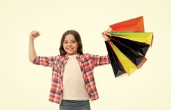 Kid strong makes independent purchases. Girl carries shopping bags isolated on white background. Girl fond of shopping royalty free stock images