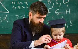 Kid studies individually with teacher, at home. Father with beard, teacher teaches son, little boy. Individual schooling. Concept. Teacher and pupil in stock photos