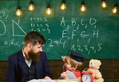 Kid studies individually with teacher, at home. Individual schooling concept. Father with beard, teacher teaches son. Little boy. Teacher and pupil in royalty free stock photos