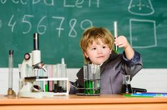 Kid study biology chemistry. Boy microscope and test tubes school classroom. Basic knowledge primary school education stock image