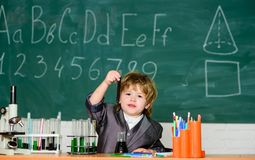 Kid study biology chemistry. Happy childhood. Child enjoy studying. Boy near microscope and test tubes in school stock photography
