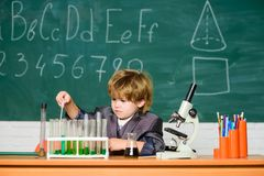 Kid study chemistry school lesson. School education. Boy use microscope and test tubes in school classroom. Toddler royalty free stock images