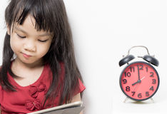 Kid Study time, Asian girl is reading a book. With a clock timing her study time Royalty Free Stock Photography