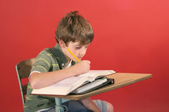 Kid studying at desk. Shot of a kid studying at desk Stock Photo