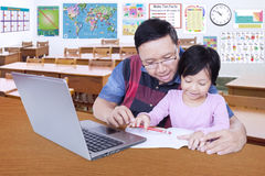Kid studying with her tutor in the classroom Stock Photos
