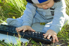 Kid studying keyboard Outdoors. Royalty Free Stock Image