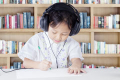 Kid studying in library while wearing headset Stock Image