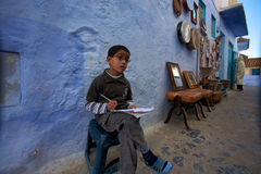 Kid studying in the street of the Blue city of Chefchaouen Stock Images