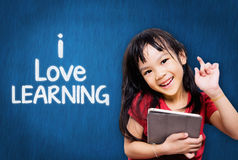 Kid studying on tablet with I love learning Royalty Free Stock Photography