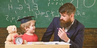 Kid studying with teacher. Father teaches son, discuss, explain. Education concept. Teacher in formal wear and pupil in. Mortarboard in classroom, chalkboard on stock photo