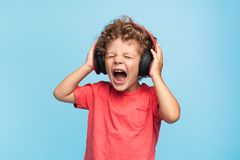 Kid suffering from loud sound. Curly boy in headphones screaming with eyes closed on blue background royalty free stock image