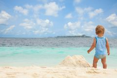 Kid, summer, beach sandbox. Toddler playing with sand on the tropical white beach Stock Image