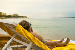 Kid sunbathing on deck chair Royalty Free Stock Photography