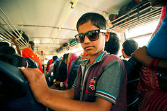 Kid in sunglasses driving inside a city bus Royalty Free Stock Photo
