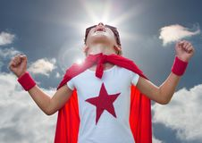 Kid in superhero costume screaming against sky in background Stock Photos