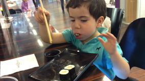 Kid swallow huge chunk of sushi stock video