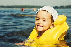 Kid with swiming vest weared. In water Stock Photos